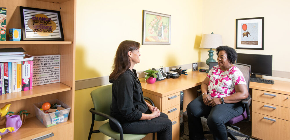 A female therapist in a pink shirt speaks to her female patient at her desk.