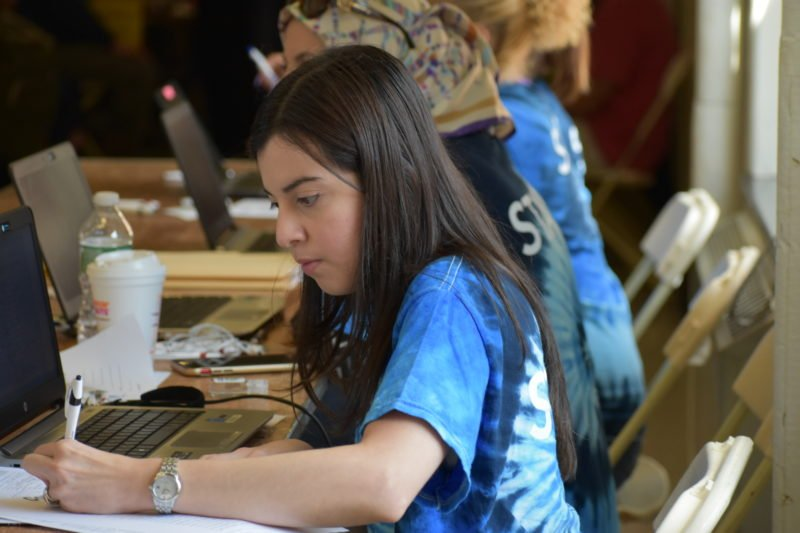 Young woman in blue tie-dye writing down a patient's information at a check-in table